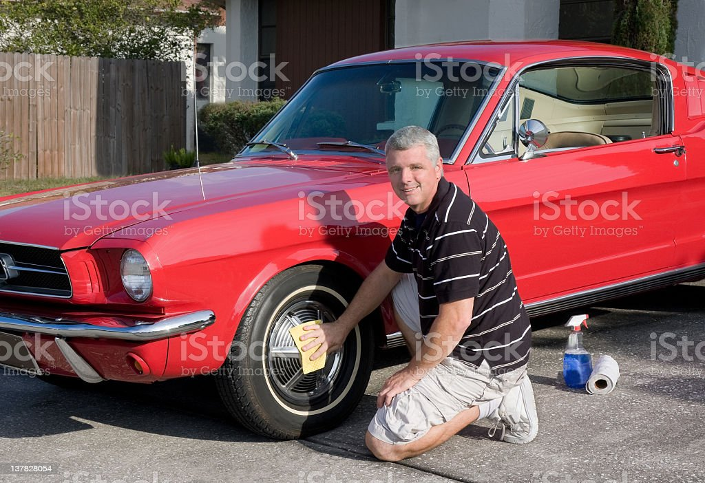 middle aged man cleaning his classic Mustang car stock photo