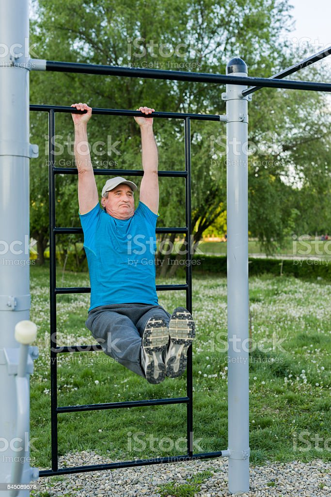 Middle aged man doing physical exercise outdoor stock photo