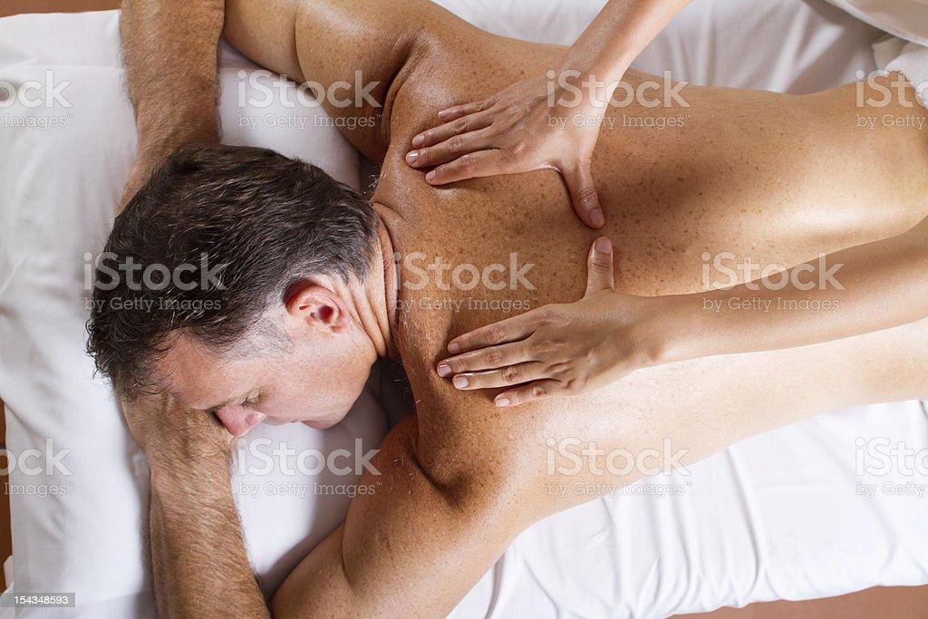 middle aged man having back massage stock photo