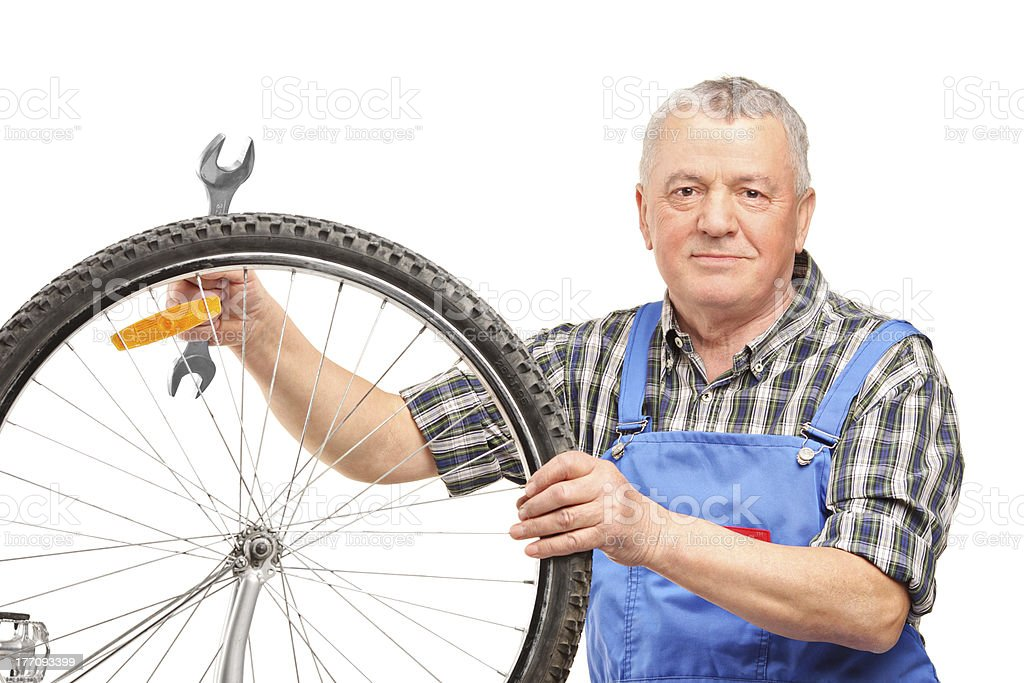Middle aged man holding wrench and repairing bicycle royalty-free stock photo