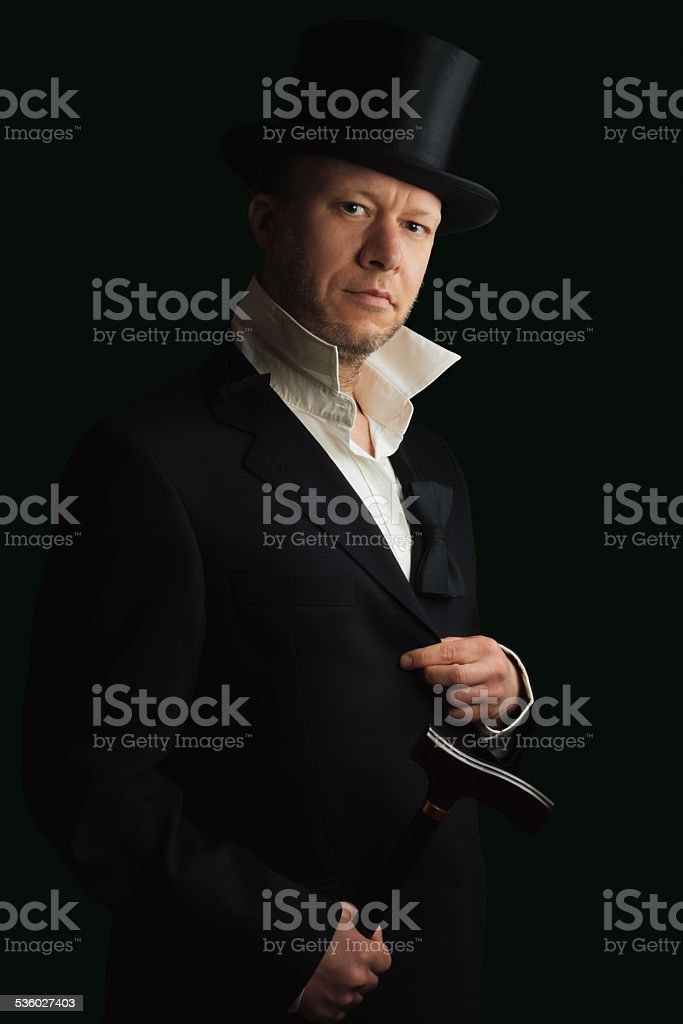 Middle aged man in suit with cane and Top Hat stock photo
