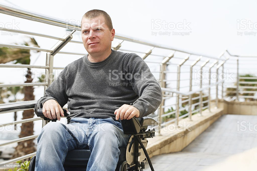 Middle aged man in wheelchair moving down ramp stock photo