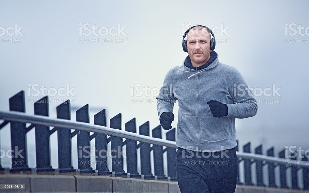 Middle aged man jogging in the city in winter stock photo