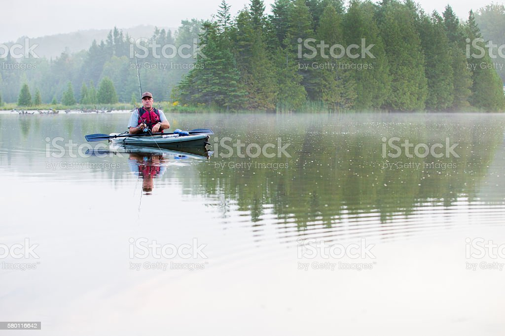 Middle aged man kayak fishing stock photo