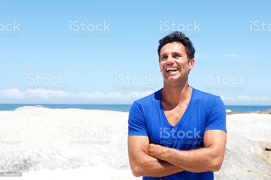 Middle aged man laughing by the beach in summer stock photo
