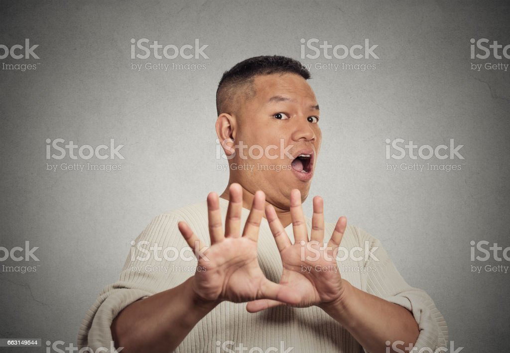middle aged  man looking shocked scared trying to protect himself stock photo
