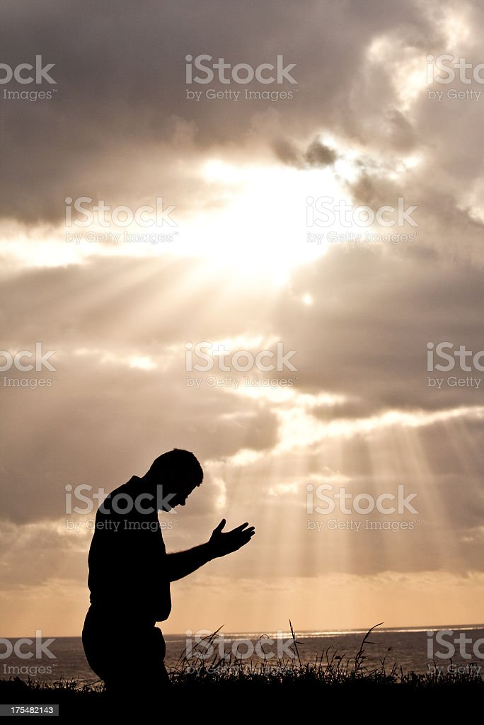 Middle Aged Man Praying Against Dramatic Sky stock photo