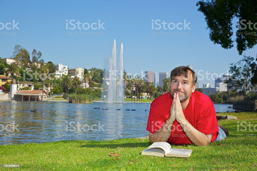 Middle Aged Man Praying with Book in Public Park royalty-free stock photo