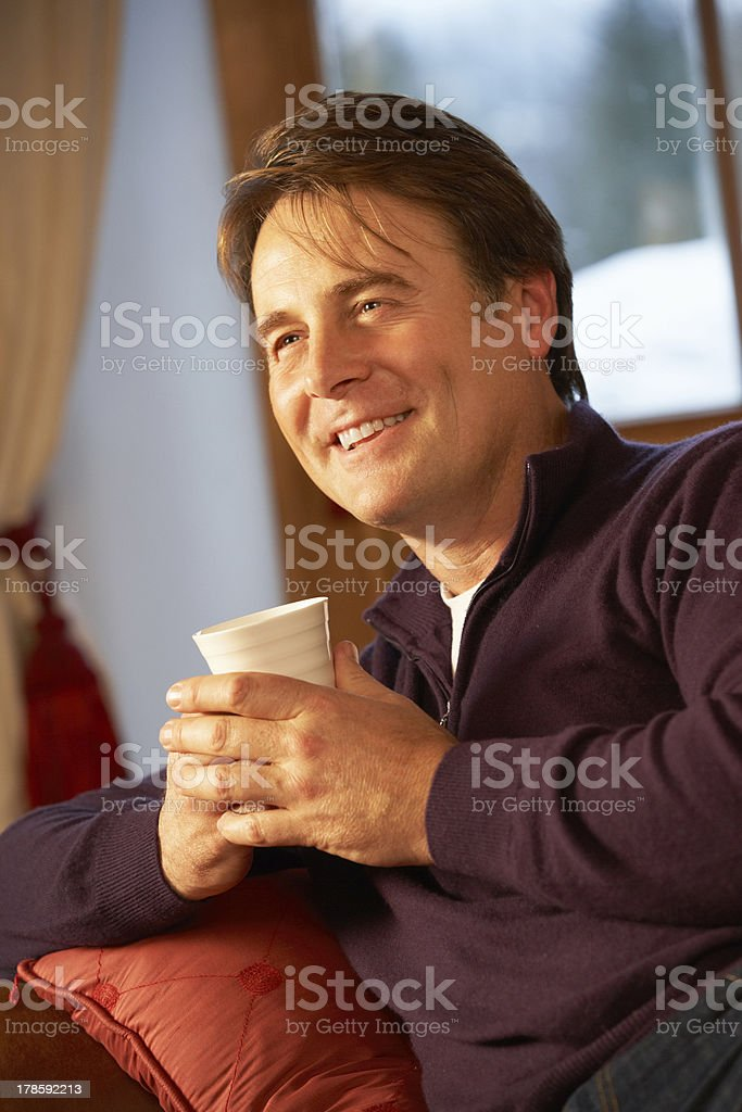 Middle Aged Man Relaxing With Hot Drink On Sofa stock photo