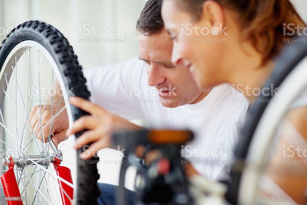 Middle aged man repairing a bicycle tyre with wife royalty-free stock photo