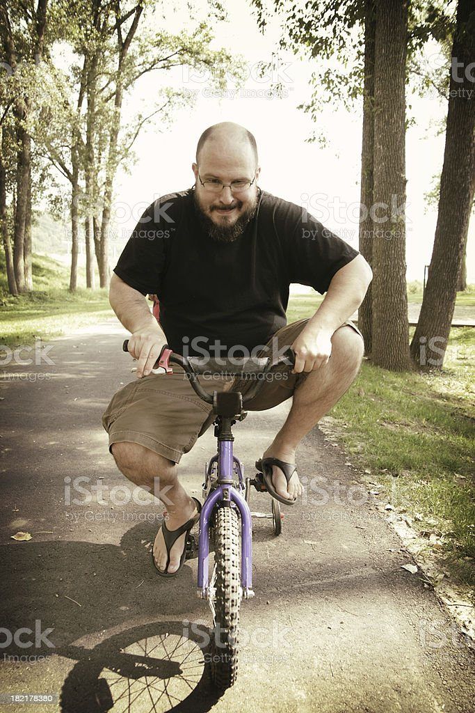 Middle Aged Man Rides Very Small Bicycle stock photo