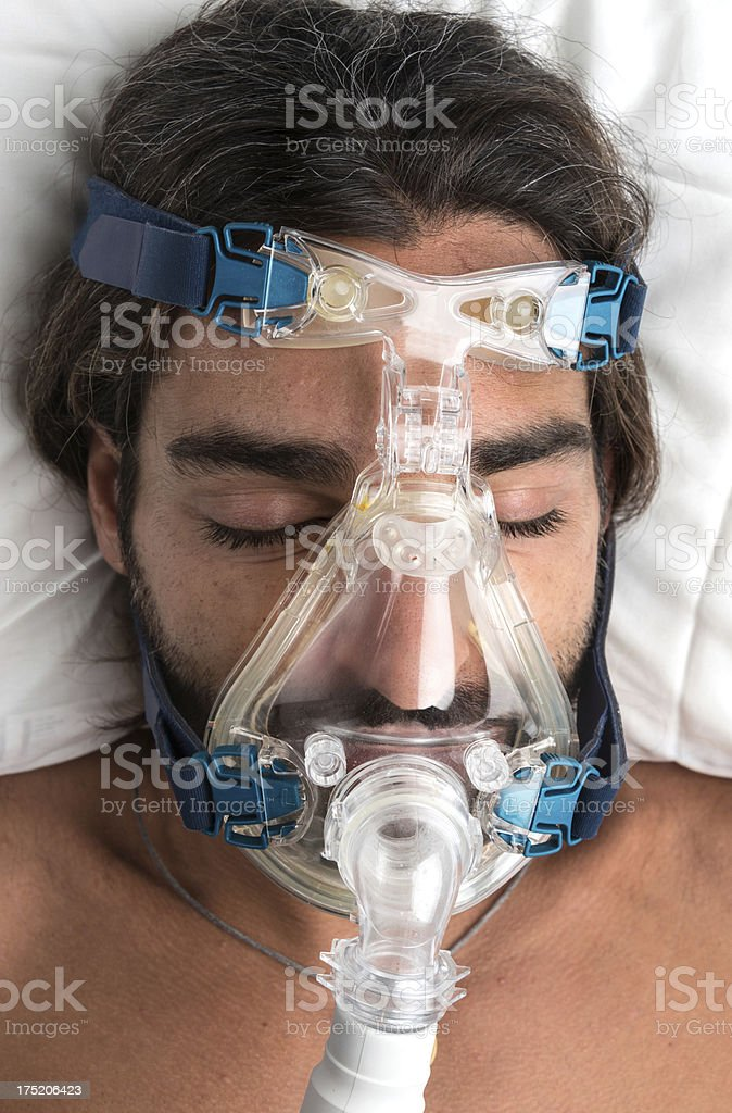 middle aged man sleeping with a mask stock photo