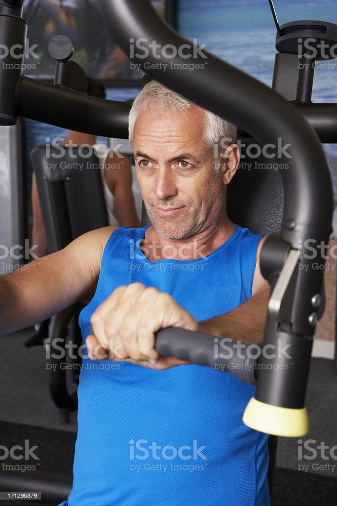 Middle Aged Man Using Weights Machine In Gym stock photo