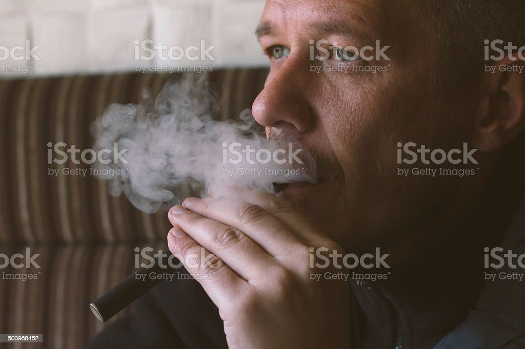 Middle aged man vaping e cigarette in cafe stock photo