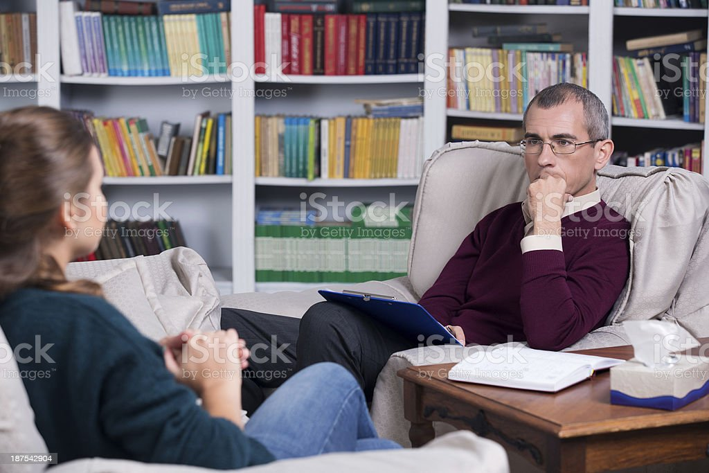 Middle aged psychoanalyst listening to a woman stock photo
