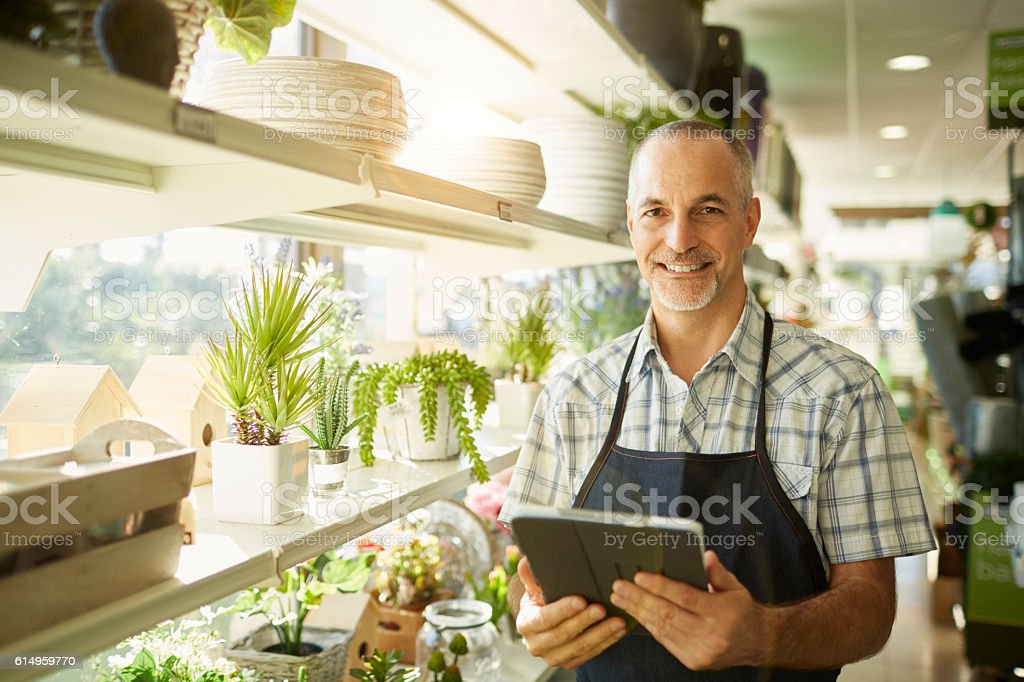 Middle aged sales clerk smiling at camera. stock photo