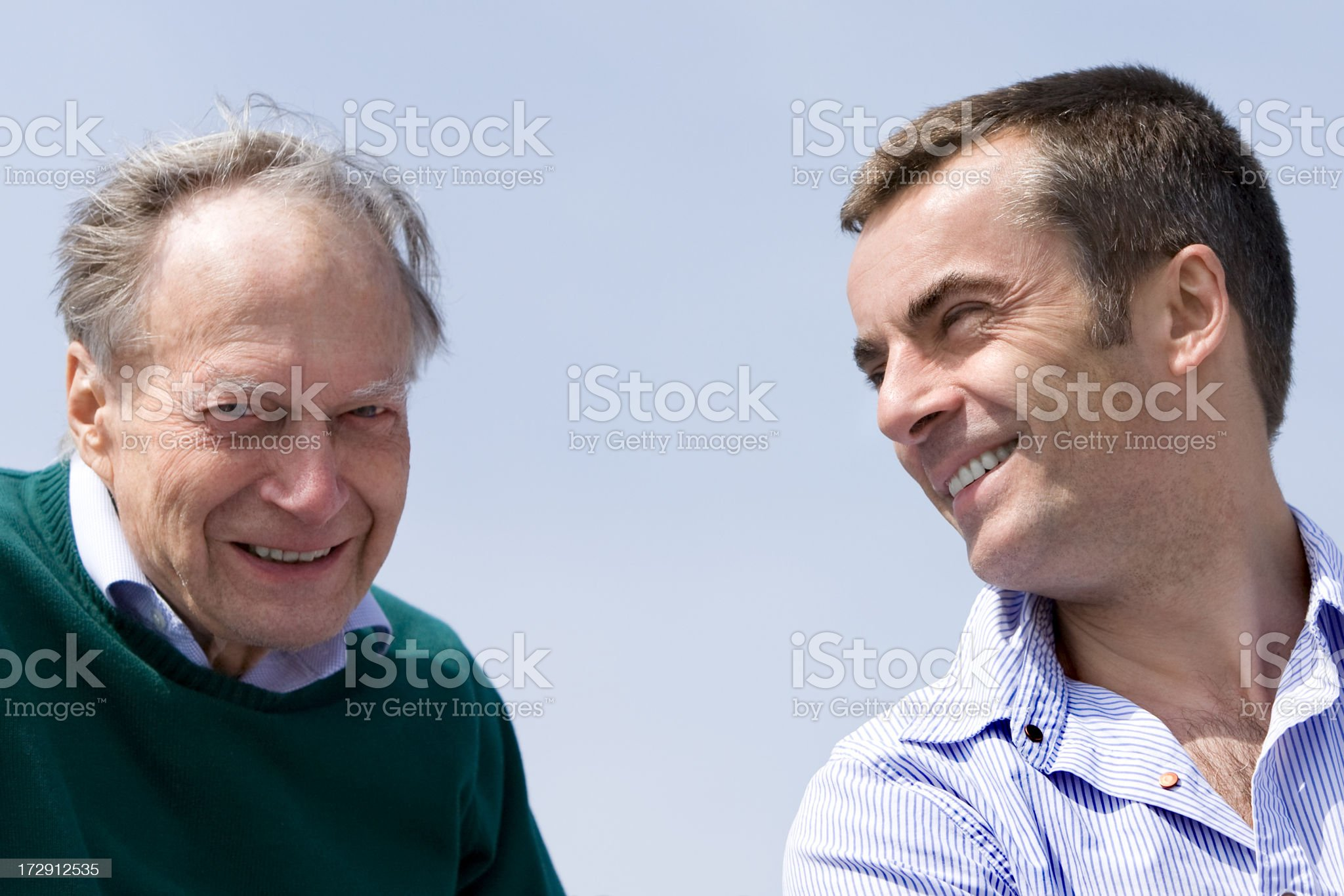 middle aged son and senior father together against blue sky royalty-free stock photo