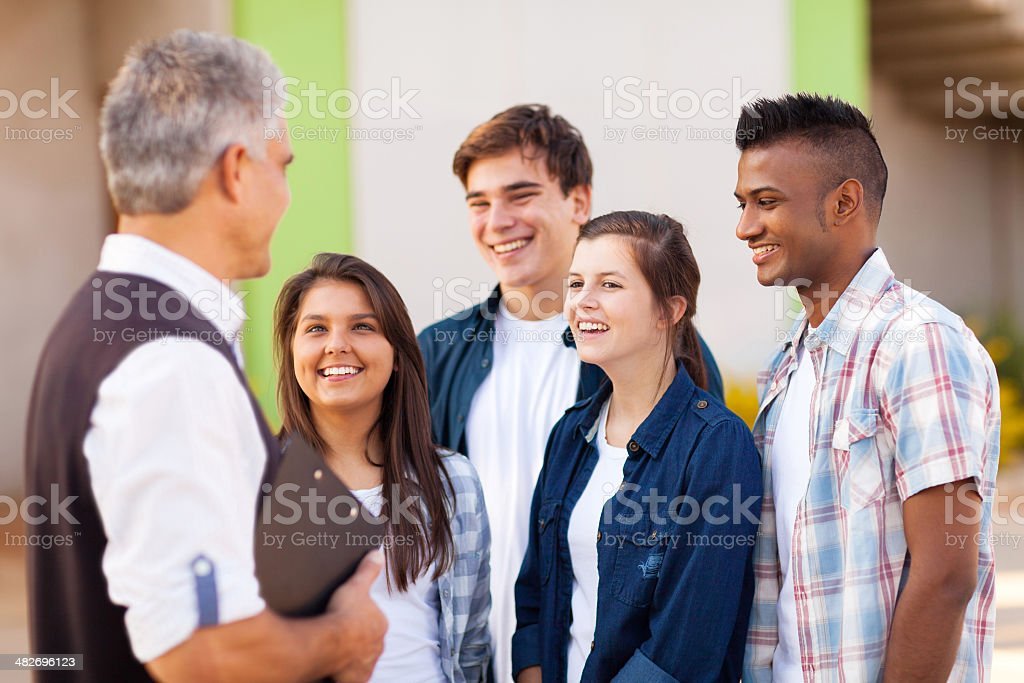 middle aged teacher talking to students stock photo