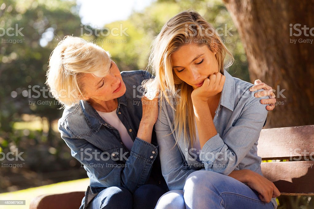 middle aged woman comforting her sad daughter stock photo