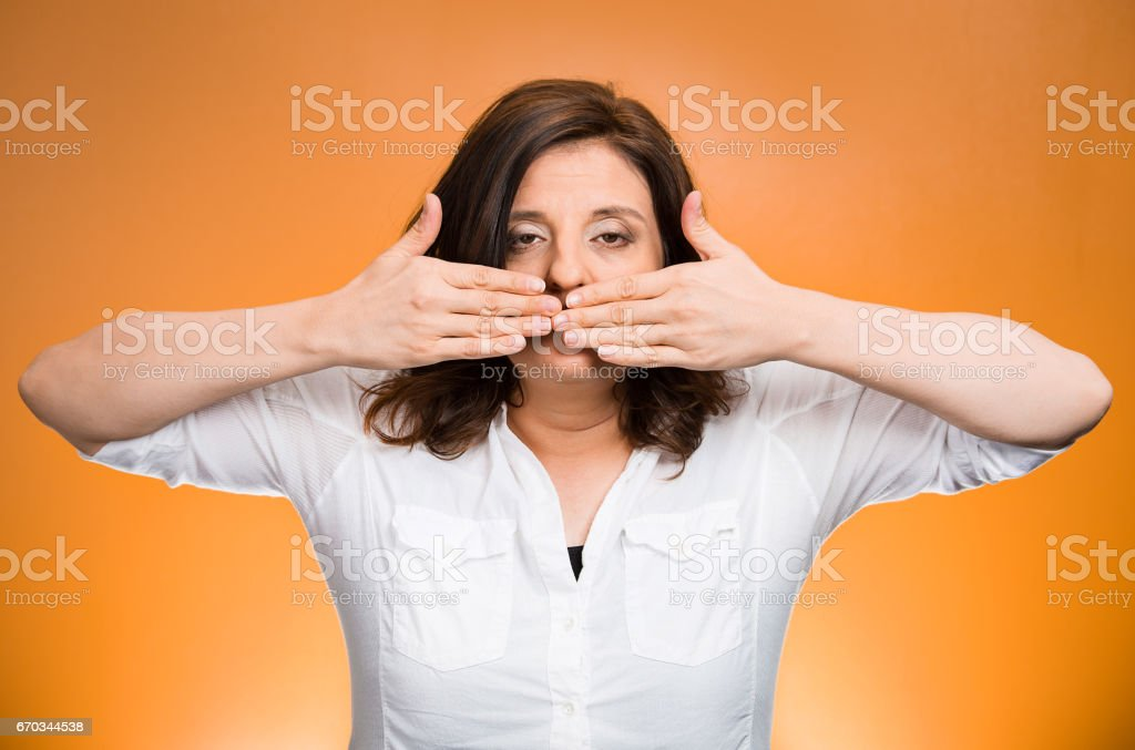 middle aged woman covering closed mouth. Speak no evil concept stock photo