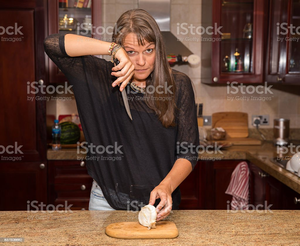 Middle aged woman cutting a white onion. stock photo