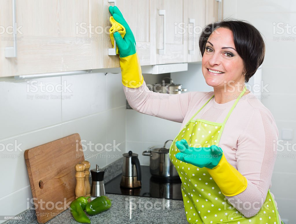 Middle aged woman dusting furniture in kitchen stock photo