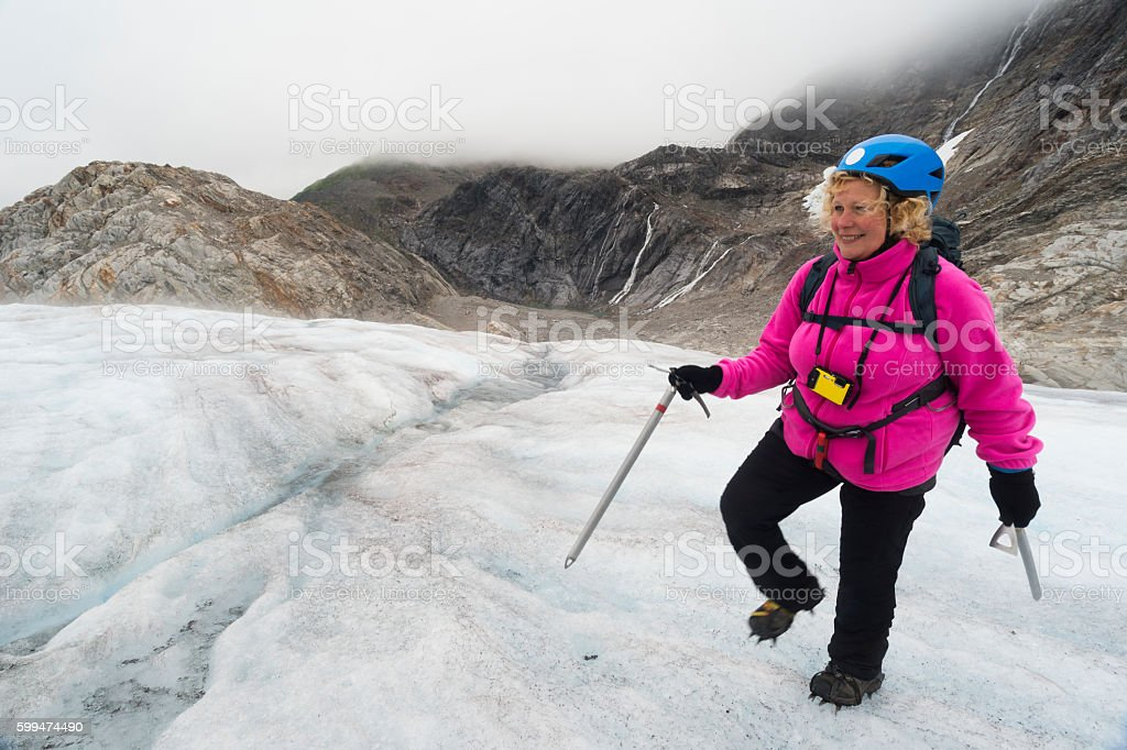 Middle aged woman explores glacier ice stock photo
