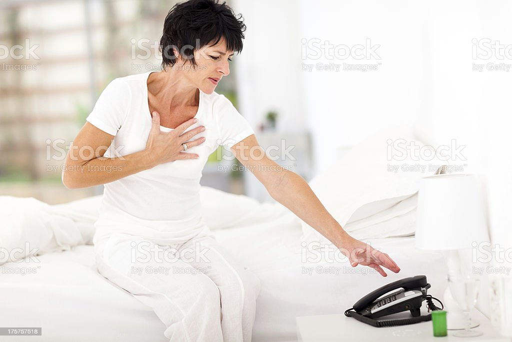middle aged woman having heart attack stock photo