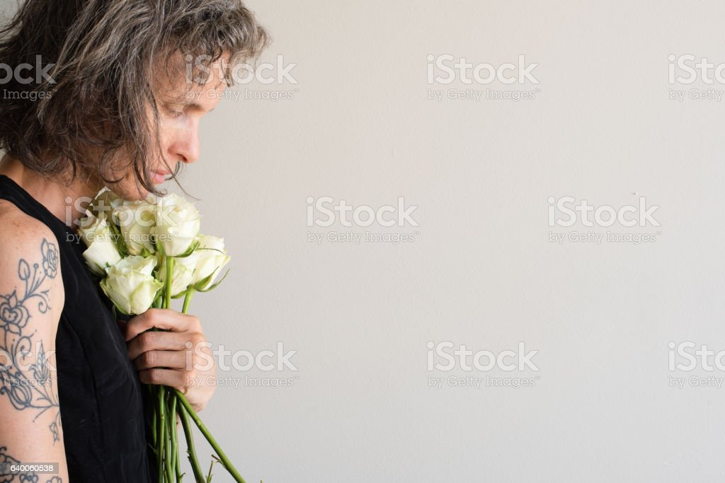 Middle aged woman holding cream roses stock photo