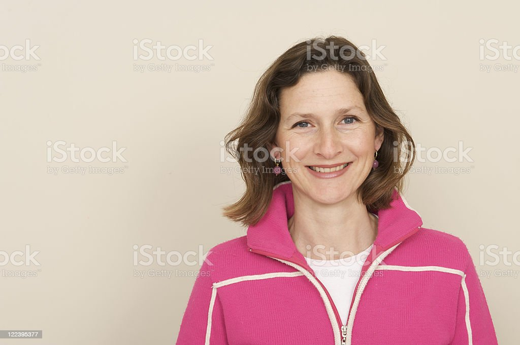 Middle aged woman in pink hooded top smiling royalty-free stock photo