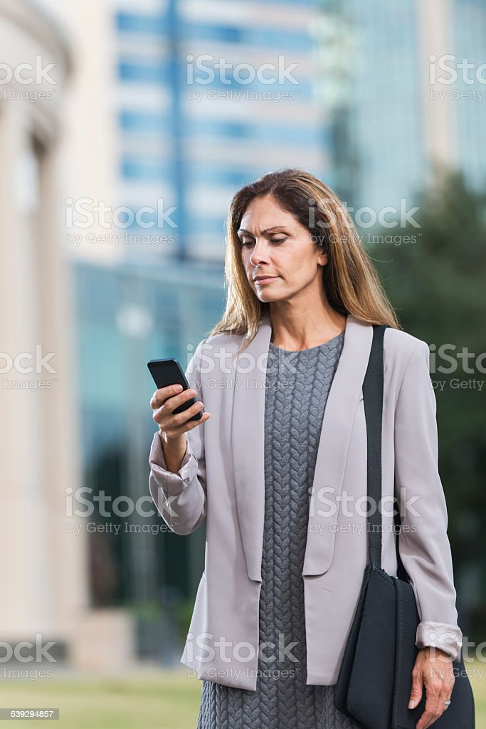 Middle aged woman looking at her mobile phone, annoyed stock photo
