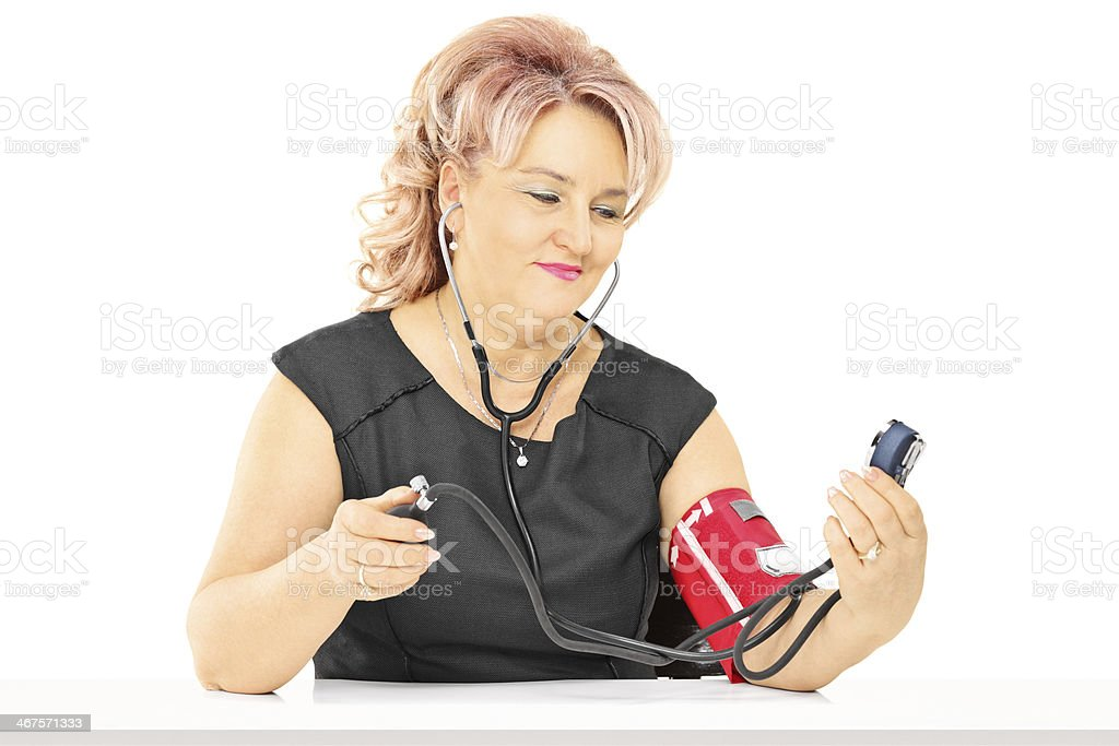 Middle aged woman measuring blood pressure royalty-free stock photo