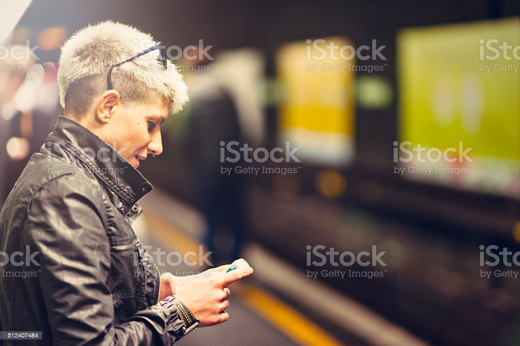 Middle aged woman messaging in metropolitan stock photo