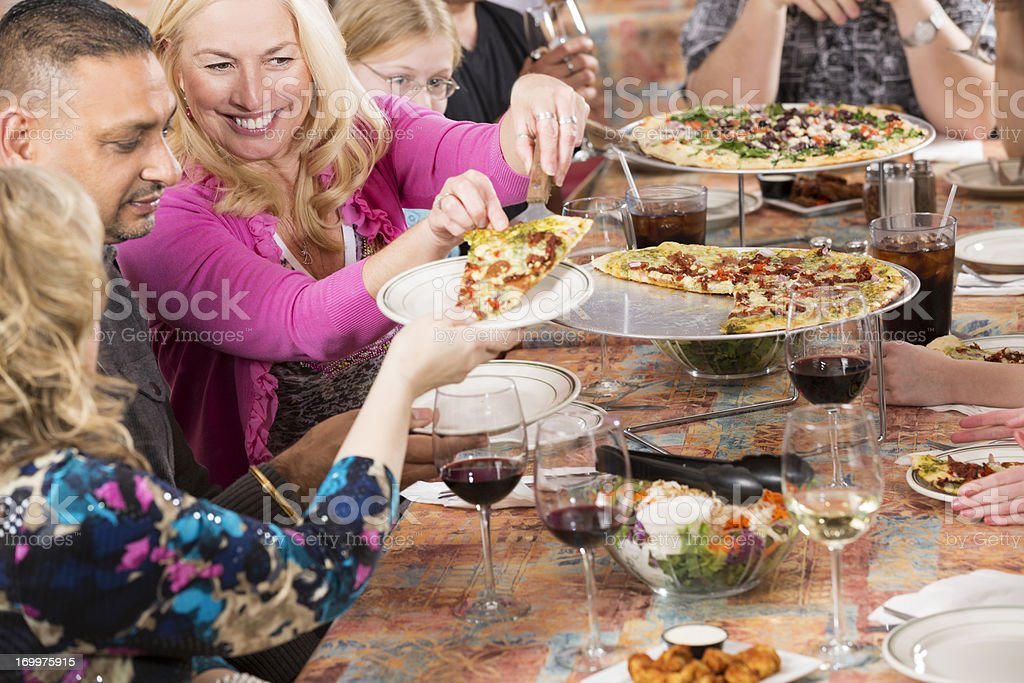 Middle aged woman passing pizza to her friends at restaurant royalty-free stock photo