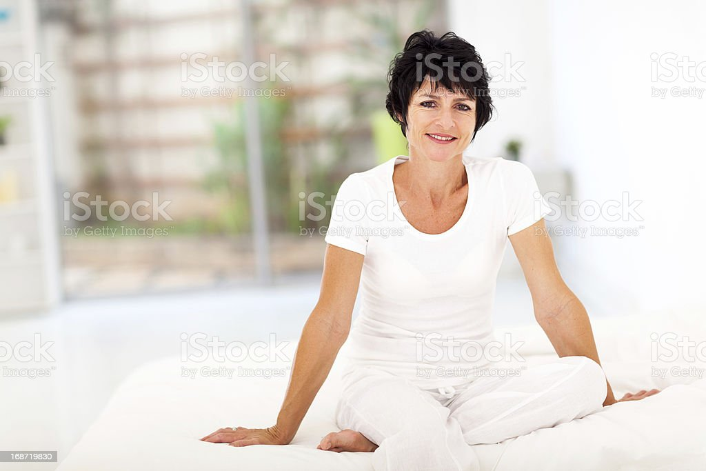 middle aged woman sitting on bed royalty-free stock photo