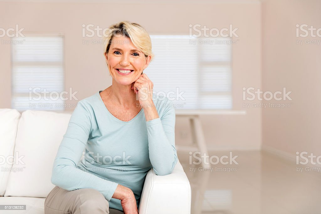 middle aged woman sitting on sofa stock photo