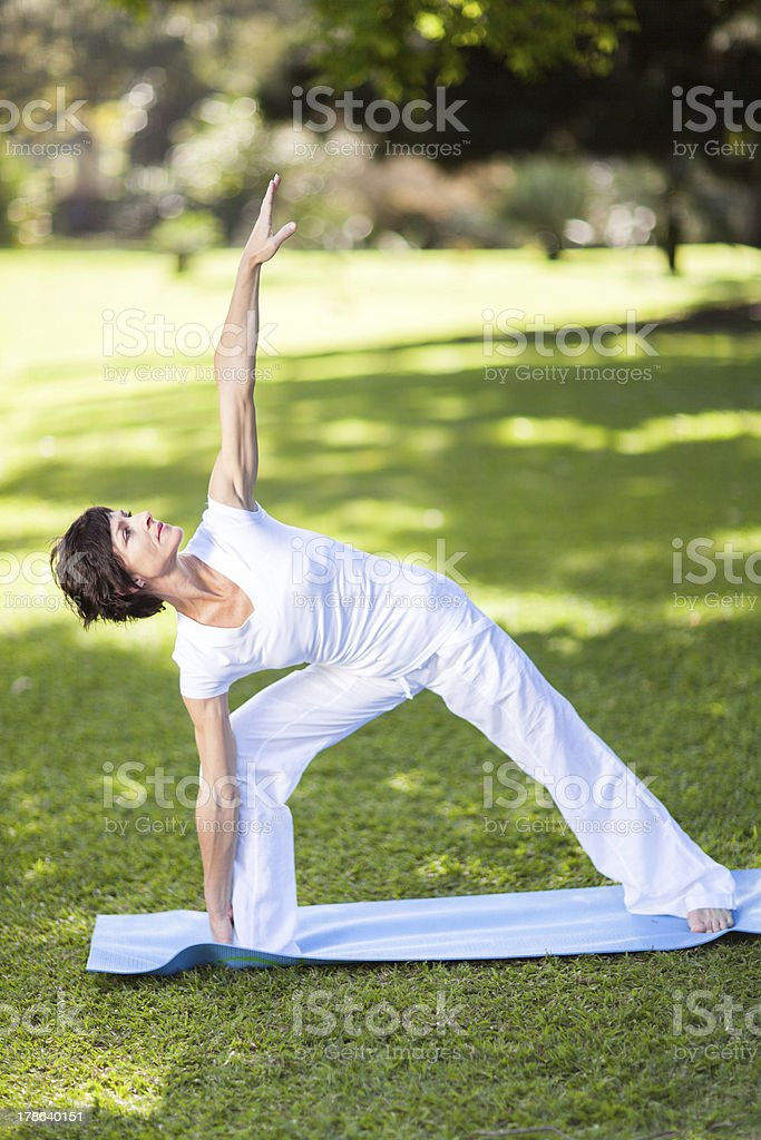 middle aged woman stretching outdoors royalty-free stock photo
