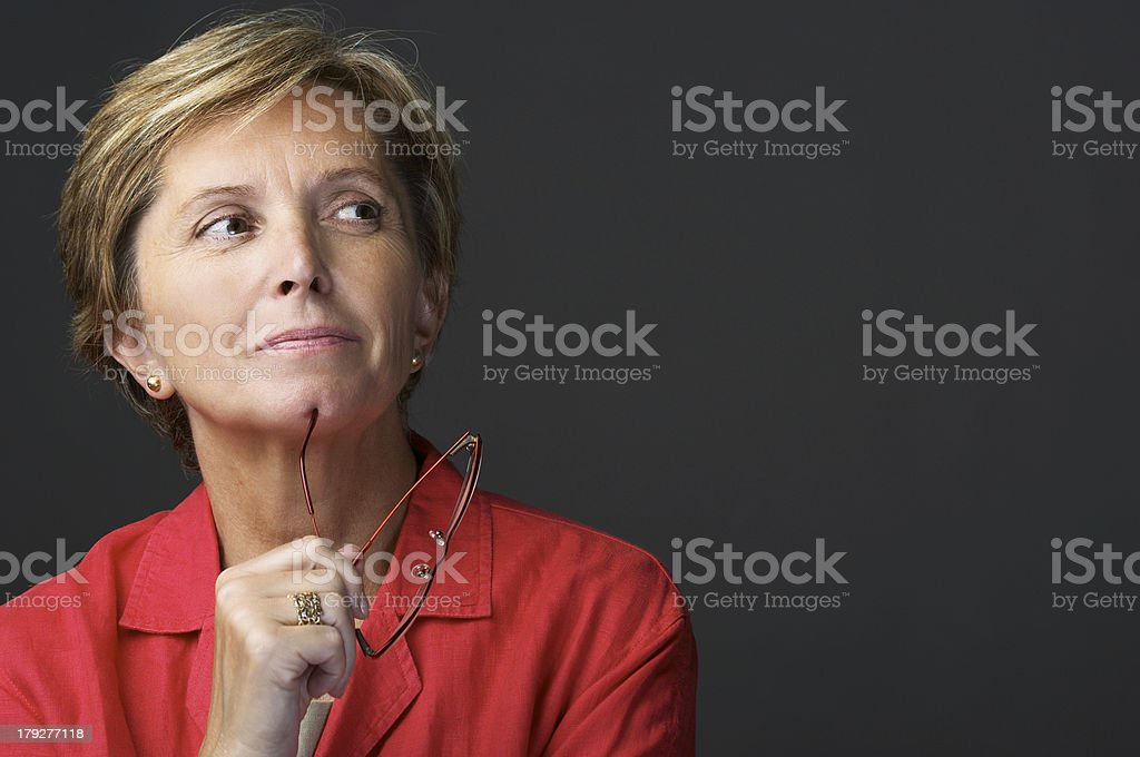 A middle aged woman thinking with her glasses in her hand stock photo