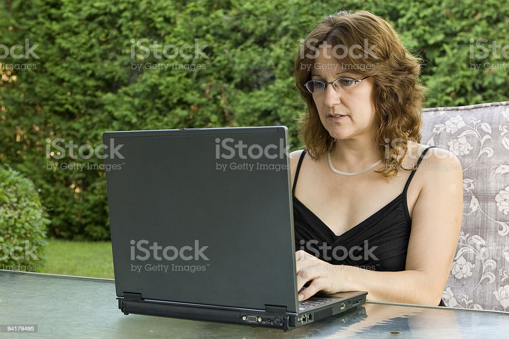 A middle aged woman using a laptop outdoors stock photo