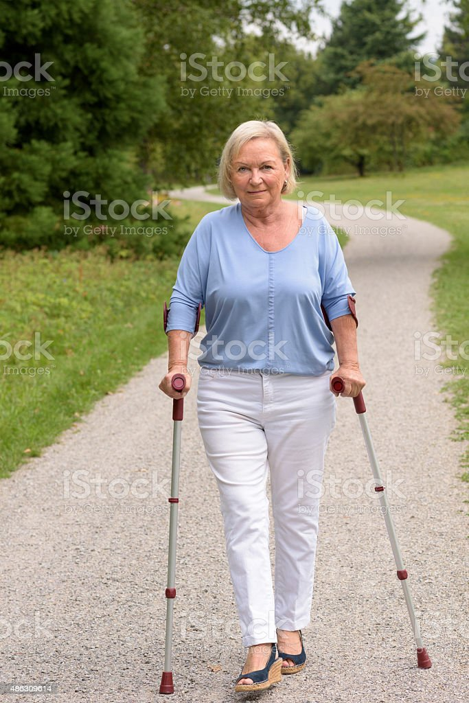 Middle Aged Woman Walking with Two Canes stock photo