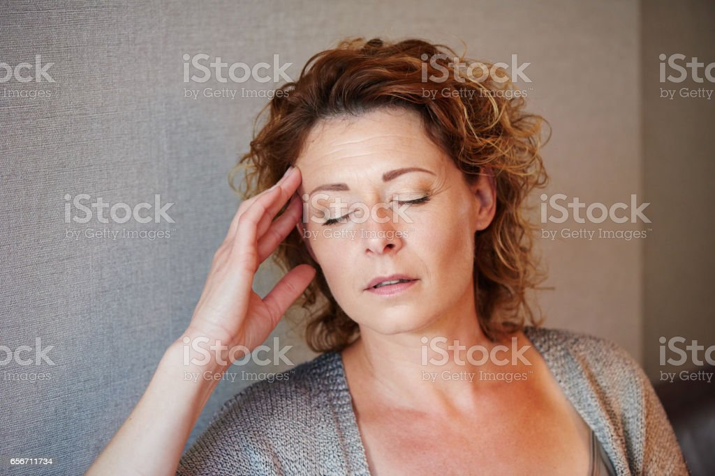 Middle aged woman with hand to head in pain stock photo