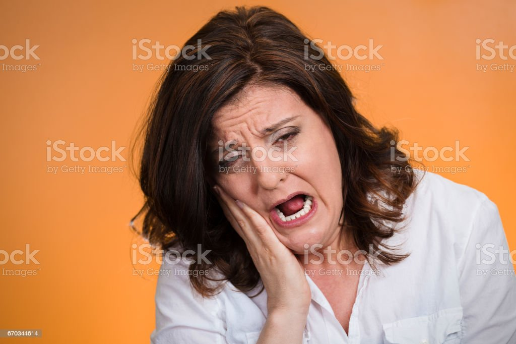 middle aged woman with sensitive tooth ache crown problem crying from pain stock photo
