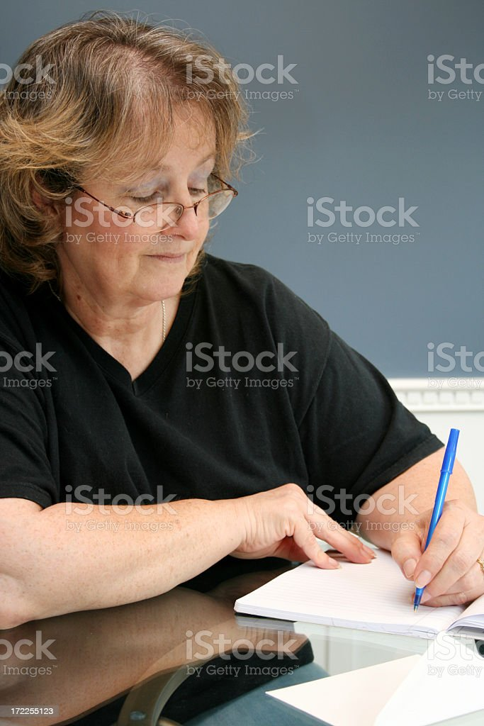 A middle aged woman writing a letter by hand  royalty-free stock photo