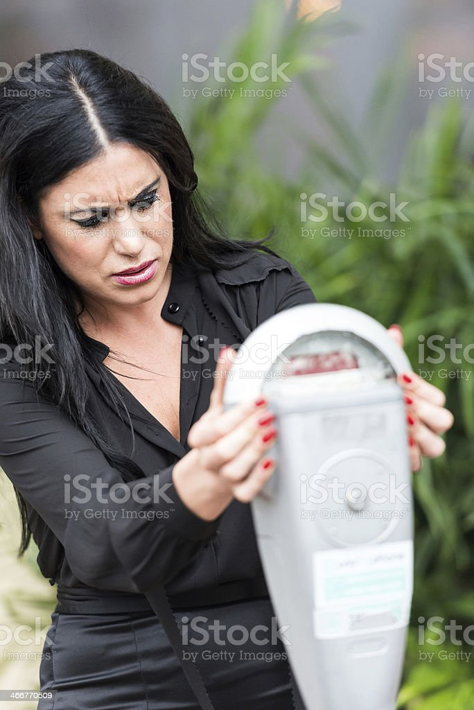 A middle aged women is frustrated with the parking meter royalty-free stock photo