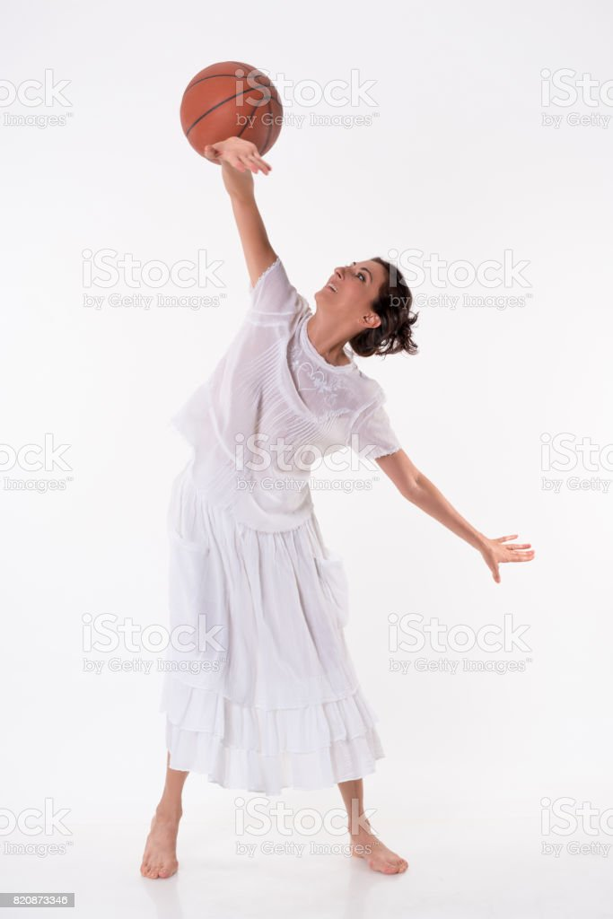 Middle aged young woman exercising with basketball stock photo