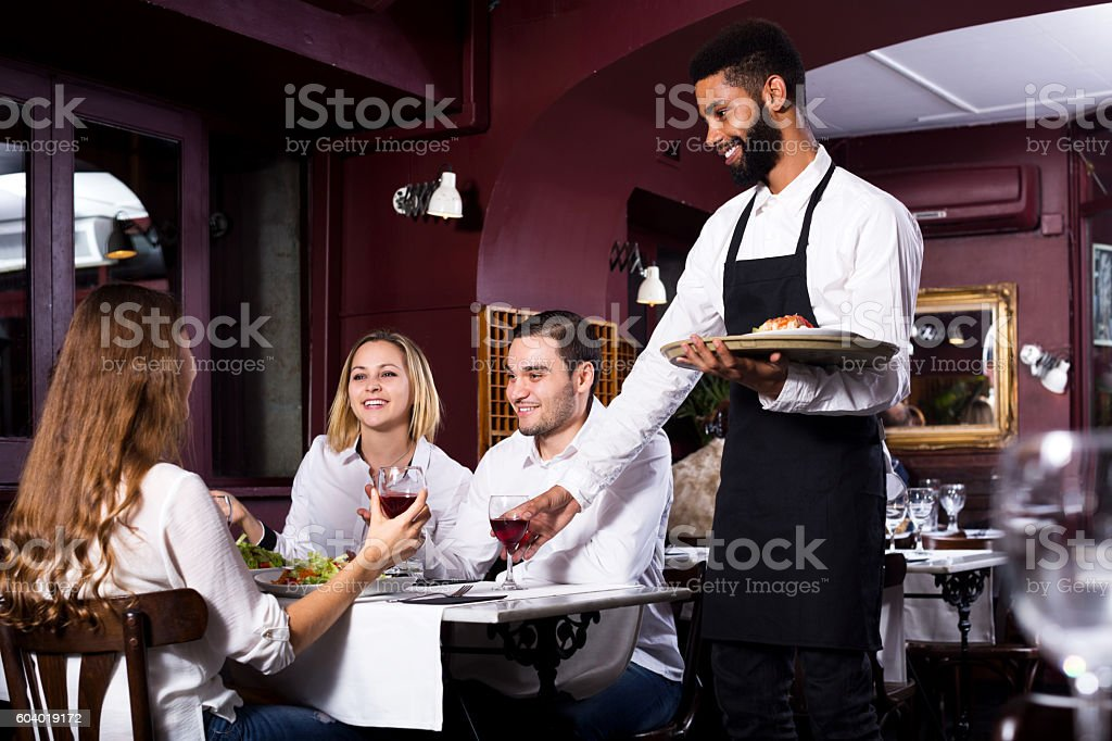 Middle class restaurant and cheerful waiter stock photo