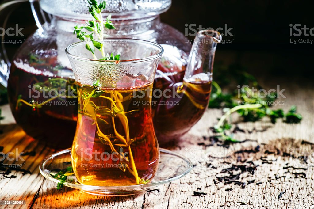 Middle East tea with thyme, ethnic glass and glass teapot stock photo