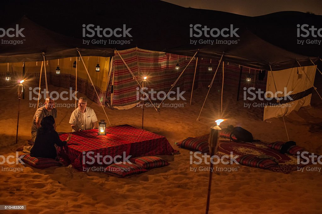 Middle Eastern and Multi-Ethnic Friends Enjoying Conversation at Desert Camp stock photo