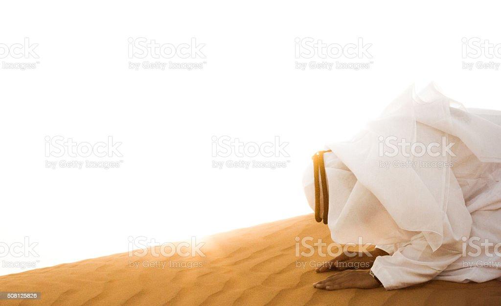Middle Eastern Arab Man Praying in Desert stock photo