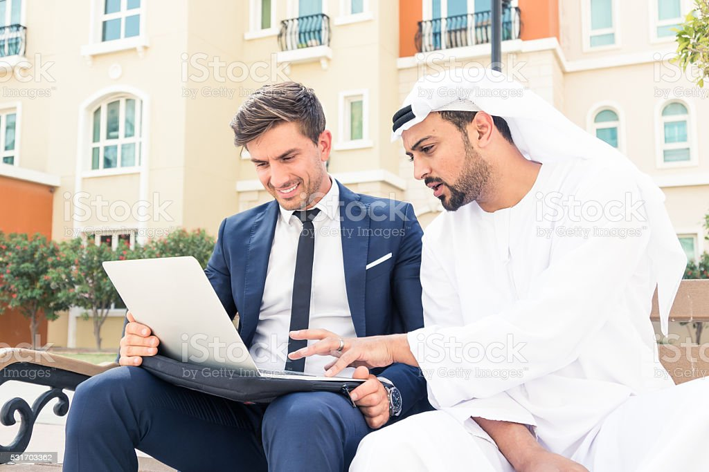 Middle Eastern Arab showing European Executive his business plan stock photo